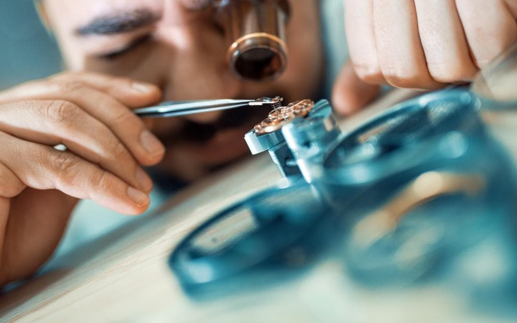 Man reparing a watch with precision tools
