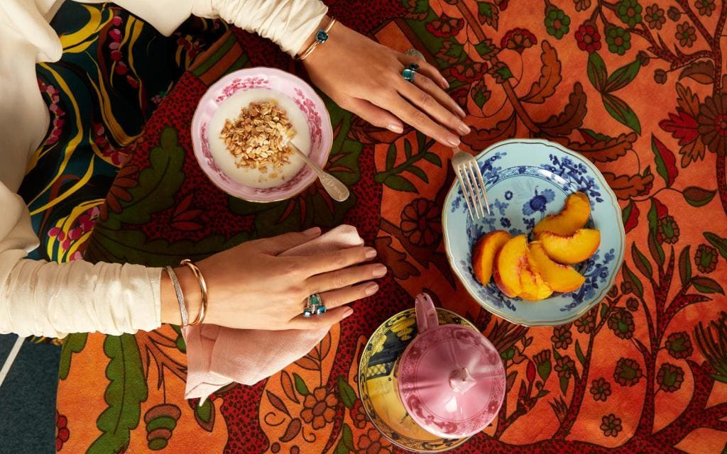 Hands on a table wearing Pomellato rings and bracelets